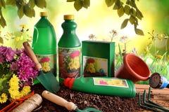 Composizione con le bottiglie ed i contenitori dei prodotti di giardinaggio dentro Immagine Stock
