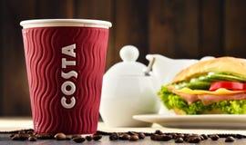 Composizione con le tazze del caffè e del panino di Costa Coffee fotografie stock