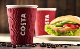 Composizione con le tazze del caffè e del panino di Costa Coffee immagine stock