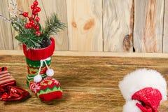 Composizione con un calzino di natale e un cappuccio di Santa di rosso, contro la bugia Fotografia Stock