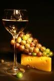 Composizione con un vetro, un formaggio e un'uva di vino Fotografia Stock