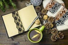 Composizione concettuale su una tavola di legno con una tazza di tè, un taccuino fatto a mano, coni di abete Immagini Stock