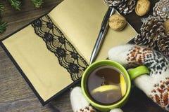 Composizione concettuale su una tavola di legno con una tazza di tè, un taccuino fatto a mano, coni di abete Fotografia Stock Libera da Diritti