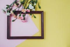 Composizione creativa con i fiori della molla Fiori bianchi e struttura di legno su fondo rosa e giallo pastello Disposizione pia fotografia stock libera da diritti