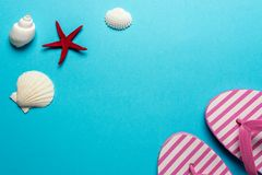 Composizione creativa con le conchiglie e le pantofole della spiaggia su fondo blu Concetto minimo di estate fotografia stock libera da diritti