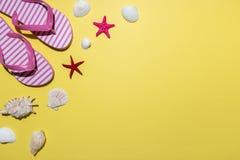 Composizione creativa con le conchiglie e le pantofole della spiaggia su fondo giallo luminoso Concetto minimo di estate immagine stock