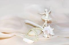 Composizione d'annata con la ballerina, le perle, i crostacei, la pietra del mare bianco e la piuma Fotografie Stock Libere da Diritti