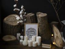 Composizione dagli abbattimenti degli alberi contro un fondo scuro, stanti su un pavimento di legno insieme alle candele e ad un' fotografie stock