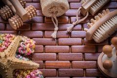Composizione degli accessori del bagno sul saun di legno controllato della tovaglietta Fotografia Stock