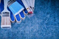 Composizione dei guanti di legno di sicurezza dei pennelli del tester su metall Immagine Stock