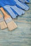 Composizione dei guanti di sicurezza dei pennelli sul constr del bordo di legno Fotografie Stock Libere da Diritti