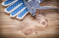 Composizione dei guanti di sicurezza della pistola della cucitrice meccanica sul bordo di legno Fotografie Stock Libere da Diritti