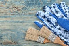 Composizione dei guanti protettivi dei pennelli sul bordo di legno co Fotografie Stock Libere da Diritti