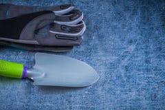 Composizione dei guanti protettivi della vanga del metallo su metall graffiato Fotografie Stock Libere da Diritti
