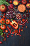Composizione dei prodotti vegetariani rossi: frutta, verdura e fagiolo su fondo di legno Apple, pomodoro, ribes, ravanello, pepe, Immagine Stock