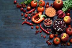 Composizione dei prodotti vegetariani rossi: frutta, verdura e fagiolo su fondo di legno Apple, pomodoro, ribes, ravanello, pepe, Fotografia Stock Libera da Diritti