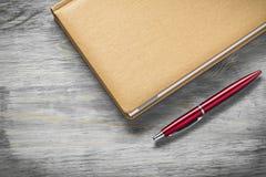 Composizione del blocco note della penna sul concetto di istruzione del bordo di legno Fotografia Stock