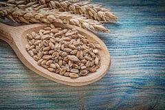 Composizione del cucchiaio di legno dei grani delle orecchie della segale del grano sul bordo di legno Immagini Stock Libere da Diritti