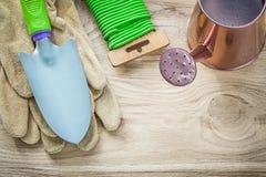 Composizione del legame molle del giardino dell'annaffiatoio dei guanti della vanga della mano sopra Fotografie Stock