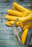 Composizione del martello da carpentiere degli abiti da lavoro di sicurezza sul const del bordo di legno Immagine Stock Libera da Diritti