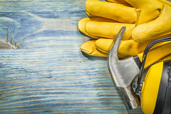 Composizione del martello da carpentiere protettivo degli abiti da lavoro sul raggiro di legno del bordo Immagini Stock