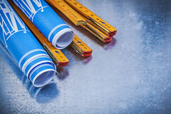 Composizione del metro di legno blu dei disegni di costruzione su metall Immagini Stock