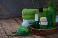 Composizione dell'aloe dei prodotti di threatment di bellezza nei colori verdi su fondo di legno marrone: sciampo, sapone, sale d Fotografia Stock