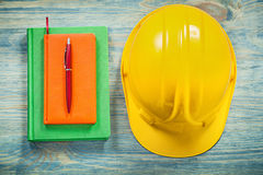 Composizione della penna dei blocchi note del casco sul constructio del bordo di legno Fotografie Stock