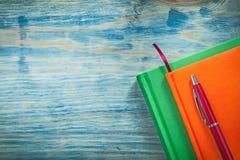 Composizione della penna dei blocchi note sul concetto dell'ufficio del bordo di legno Fotografia Stock