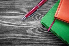 Composizione della penna a sfera dei blocchi note sul bordo di legno d'annata Immagine Stock