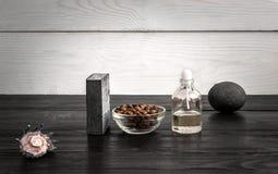 Composizione delle bottiglie e del sapone di olio su fondo di legno nero Fotografia Stock