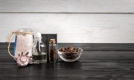 Composizione delle bottiglie e del sapone di olio su fondo di legno nero Immagine Stock Libera da Diritti