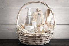 Composizione delle bottiglie e della merce nel carrello cosmetiche del sapone, su fondo di legno bianco Immagine Stock