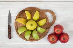 Composizione delle mele differenti di colore sul tagliere e sul coltello di legno accanto nella vista superiore Immagini Stock Libere da Diritti