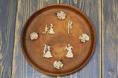 Composizione delle riunioni romantiche dalle figure di legno d'annata e dai fiori decorativi da raso sul piatto ceramico Di legno immagini stock libere da diritti