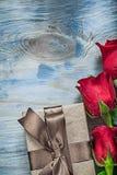 Composizione delle rose rosse avvolte del contenitore di regalo sul celebr del bordo di legno Fotografia Stock Libera da Diritti