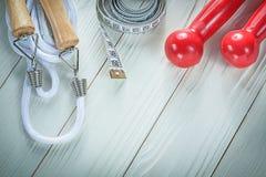 Composizione delle teste di legno della corda di salto che misurano nastro sulla b di legno Fotografie Stock Libere da Diritti