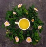 Composizione di estate della tazza dei rami della rosa canina e del tè e dei fiori sulla tavola di marmo scura, disposizione pian Fotografia Stock Libera da Diritti