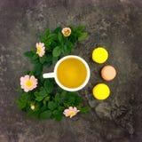 Composizione di estate della tazza dei rami della rosa canina e del tè e dei fiori sulla tavola di marmo scura, disposizione pian Fotografie Stock Libere da Diritti