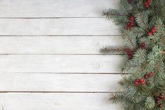 Composizione di Natale dei rami dell'abete e delle bacche del viburno su un fondo di legno bianco Vista superiore con lo spazio d fotografia stock