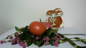 Composizione di Pasqua dei fiori, delle uova rosse e del coniglietto Immagine Stock