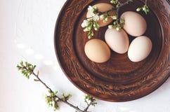 Composizione di Pasqua delle uova su un piatto e sui ramoscelli dell'argilla con la fioritura immagini stock