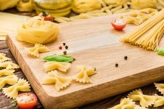 Composizione di pasta asciutta, di pepe nero, di basilico e dei pomodori Fotografie Stock