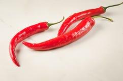 Composizione di peperoncino/di composizione rossi di peperoncino rosso su un fondo bianco fotografia stock