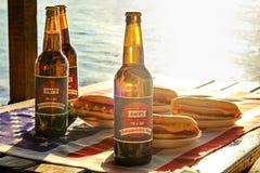Composizione in festa con le bottiglie multiple di birra e dei hot dog, bandiera americana Celebrazione della festa dell'indipend Fotografia Stock