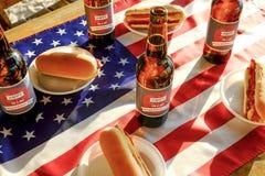 Composizione in festa con le bottiglie multiple di birra e dei hot dog, bandiera americana Celebrazione della festa dell'indipend Immagini Stock Libere da Diritti