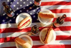 Composizione in festa con le bottiglie multiple di birra e dei hot dog, bandiera americana Celebrazione della festa dell'indipend Fotografia Stock Libera da Diritti