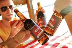 Composizione in festa con le bottiglie multiple di birra e dei hot dog, bandiera americana Gruppo di persone che celebrano festa  Immagine Stock