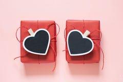 Composizione in giorno di S. Valentino: due contenitori di regalo rossi con la molletta da bucato come cuore con spazio per testo immagini stock libere da diritti