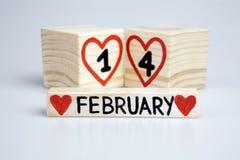 Composizione in giorno di Valentine's con il calendario di legno 14 febbraio scritto a mano, cuori rossi Fotografia Stock